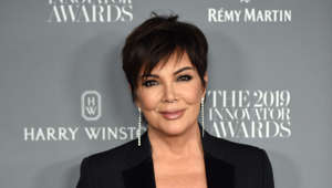 Kris Jenner holding a sign posing for the camera