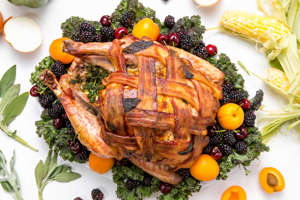 a plate of food with broccoli: Tired of your usual Thanksgiving turkey recipe? Give your holiday bird a bacon-wrapped update, with this recipe inspired by Better Homes & Gardens, and watch your family and friends drool when you bring it to the table!