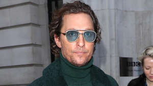 Matthew McConaughey wearing sunglasses and standing in front of a building
