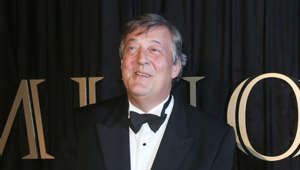 Stephen Fry wearing a suit and tie
