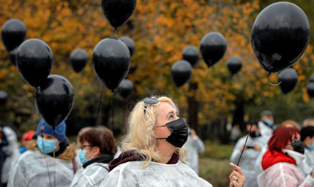 Slide 1 of 23: Medical workers, wearing masks for protection against the COVID-19 infection, hold black balloons in memory of those who lost their lives while in the care of the state health system in Bucharest, Romania, Tuesday, Nov. 17, 2020. A fire last week at a hospital treating COVID-19 patients in northeastern Romania killed 11 people who were intubated in the intensive care unit. (AP Photo/Vadim Ghirda)