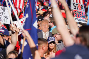 "Donald Trump et al. standing in front of a crowd: A supporter of President Trump holds a cutout of him during a ""Stop the Steal"" rally outside the Georgia Capitol in downtown Atlanta on Nov. 21. (Kevin D. Liles for The Washington Post)"