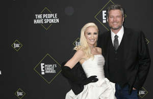Gwen Stefani, Blake Shelton holding a sign posing for the camera: Gwen Stefani and Blake Shelton