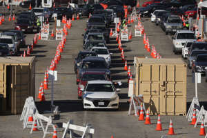a street filled with lots of traffic: A driver receives a testing kit at a Curative Inc. Covid-19 drive-thru testing site in the parking lot of Dodger Stadium in Los Angeles, California, U.S., on Friday, Nov. 13, 2020. California passed the grim milestone of 1 million infections as the U.S. Centers for Disease Control and Prevention said almost no part of the country is being spared in the surge.