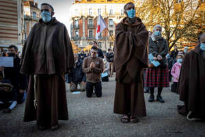 a group of people wearing costumes: Monks and Catholic faithful take part in a rally to protest COVID-19 restrictions under which masses are banned in churches, on Nov. 22, 2020, outside the Saint-Etienne cathedral in Toulouse, southern France, during a second national lockdown in France aimed at curbing the spread of the COVID-19 pandemic, caused by the novel coronavirus.