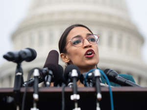 a man standing in front of a building: US Representative Alexandria Ocasio-Cortez, Democrat of New York, speaks during a press conference calling on Congress to cut funding for US Immigration and Customs Enforcement (ICE) and to defund border detention facilities, outside the US Capitol in Washington, DC, February 7, 2019. SAUL LOEB/AFP via Getty Images