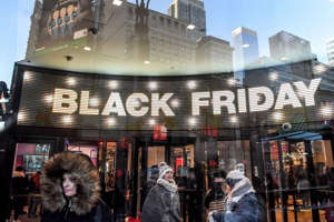 a group of people standing in front of a store: A marquee outside of Macy's flagship store in New York City during Black Friday 2018.