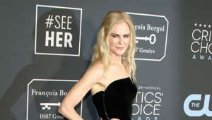 Nicole Kidman holding a sign posing for the camera