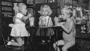 a little girl sitting on a table: Two girls and a boy drinking ice cream floats at a drug store in Florida, circa 1955. (Photo by FPG/Archive Photos/Getty Images)