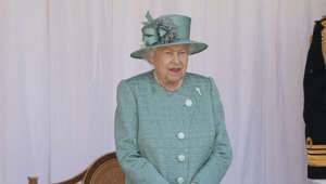 Elizabeth II standing in front of a curtain