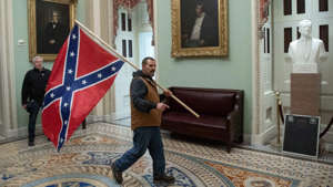 a man standing in front of a building: Man photographed carrying Confederate flag in Capitol arrested