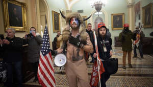 a group of people posing for the camera: Authorities say Jacob Anthony Chansley was seen at the Capitol shirtless and wearing a horned headdress.
