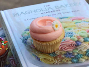 a cake with fruit on top of a paper plate: The Carrie Cupcake is a vanilla cupcake with pink pastel vanilla buttercream. Magnolia Bakery