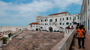 a group of people walking in front of Cape Coast Castle: A visit to the Cape Coast Castle in Ghana is a painful but necessary reminder of the Atlantic slave trade that went on for centuries.