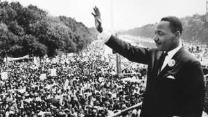 Martin Luther King, Jr. in a suit standing in front of a crowd: Black American civil rights leader Martin Luther King (1929 - 1968) addresses crowds during the March On Washington at the Lincoln Memorial, Washington DC, where he gave his 'I Have A Dream' speech.  (Photo by Central Press/Getty Images)