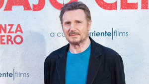 Liam Neeson holding a sign posing for the camera