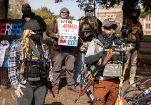 a group of people walking down a dirt road: Armed people rally for gun rights at the Capitol on Sunday Jan. 17, 2021 in Austin, Texas.