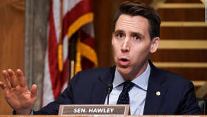 Josh Hawley wearing a suit and tie: Sen. Josh Hawley (R-MO) asks questions during a Senate hearing.