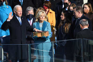 Joe Biden, Jill Biden standing in front of a crowd: President Joe Biden is sworn in during the 2021 Presidential Inauguration.