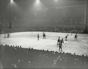 a group of people riding skis on a snowy surface: The game of hockey has a long, storied history, from the frozen ponds of Europe and North America to packed arenas around the world. Here's a series of snapshots of how this beloved game has evolved over the decades.