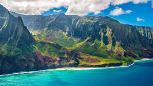 a body of water with Na Pali Coast State Park in the background: Hawaii is like nowhere else in the United States