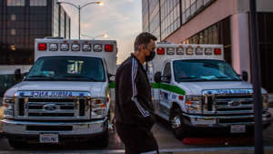 a man in a police car parked in front of a truck: Health officials estimate one in three LA County residents have been infected by coronavirus