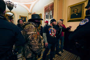 a group of people standing in a room: Doug Jensen (C), 41, of Des Moines and other Pro-Trump rioters confront U.S. Capitol Police officers in a hallway near the Senate chamber at the Capitol in Washington, Wednesday, Jan. 6, 2021. Jensen was arrested by the FBI at 1 a.m. on Saturday, Jan. 9, 2021.