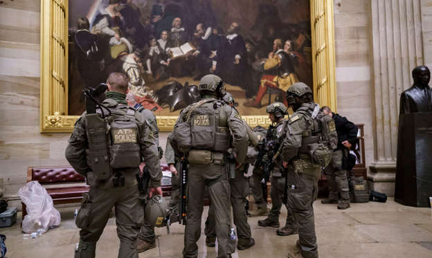 a group of people standing in front of a military uniform: After violent protesters loyal to President Donald Trump stormed the U.S. Capitol today, a tactical team with ATF gathers in the Rotunda to provide security for the continuation of the joint session of the House and Senate to count the Electoral College votes cast in November's election, at the Capitol in Washington, Wednesday, Jan. 6, 2021.