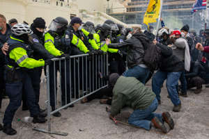 a group of people standing in front of a crowd: Rioters clash with police outside the Capitol on Jan. 6.