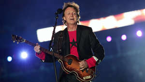 a person standing on a stage: On an X-shaped stage made of video projectors, Sir Paul McCartney first warmed up with 'Drive My Car.' He then followed up with 'Get Back,' before trading his guitar for a piano during a fireworks-laden rendition of 'Live and Let Die.' Saving for the best for last, the former Beatles member, closed with 'Hey Jude,' where the 84,000 in attendance at Jacksonville's Alltel Stadium all joined in.