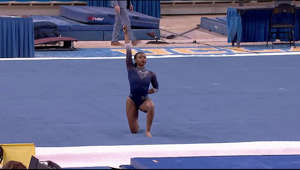 a woman standing on a court: UCLA gymnast Nia Dennis clinches the win for the Bruins with a 9.95 on floor exercise against Arizona State on Jan. 23, 2021