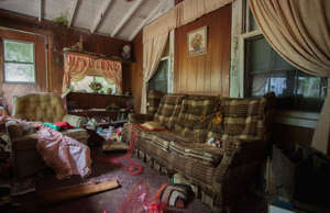 a living room filled with furniture and a fireplace: Once a grand family home, this mysterious property in America's Deep South has stood vacant for some 40 years. Untouched for decades, it offers a fascinating snapshot of domestic life back in the 1980s. Captured by photographer Leland Kent of Abandoned Southeast, click or scroll through and let's step inside and uncover the secrets of this enigmatic home's past life...