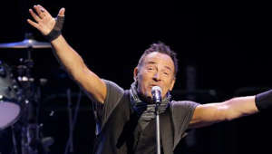Bruce Springsteen holding a guitar on a stage: Bruce Springsteen's DWI charge gets dropped, pleads guilty to alcohol consumption