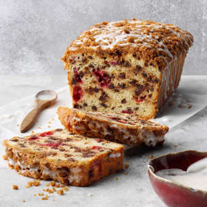 a half eaten piece of cake on a plate: This cranberry quick bread has a few components: the batter, streusel and a glaze. Each, though, is simple to make, and once assembled this loaf is as impressive as it is easy. Plus, it can double as a dessert! Get Recipe Check out these other cranberry bread recipes.