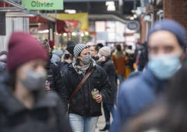 a group of people walking down a street: People wear face masks as they walk through a market in Montreal, Sunday, March 14, 2021, as the COVID-19 pandemic continues in Canada and around the world. THE CANADIAN PRESS/Graham Hughes