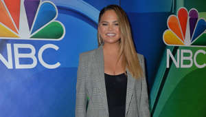 Chrissy Teigen wearing a green shirt