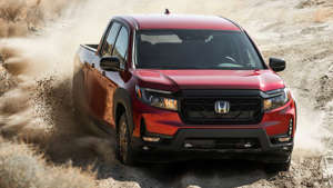 a car driving down a dirt road: 2021 Honda Ridgeline Sport Exterior Front Quarter