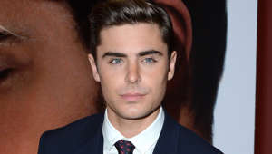 Zac Efron wearing a suit and tie looking at the camera