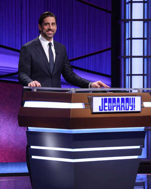 "Aaron Rodgers in a suit standing in front of a window: Green Bay Packers quarterback Aaron Rodgers is the latest guest host of ""Jeopardy!"" He'll read clues on episodes airing April 5-16."