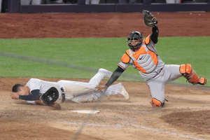 a baseball player swinging a bat at a ball: April 7: Baltimore Orioles catcher Pedro Severino tags out New York Yankees third baseman Gio Urshela in the 11th inning to end the game.
