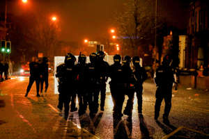 Police officers standing behind shields walk along Springfield Road as protests continue in Belfast, Northern Ireland, April 7, 2021. REUTERS/Jason Cairnduff    REFILE - QUALITY REPEAT
