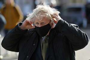 British Prime Minister Boris Johnson wearing a protective mask arrives to visit Ann's Cottage Surf Shop in Truro, Cornwall, Britain April 7, 2021. Justin Tallis/Pool via REUTERS