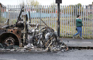 A woman walks past a burnt out bus on the Shankill road in West Belfast, Northern Ireland, Thursday, April 8, 2021. The scene follows another night of violence in Loyalist areas that has now spread to interface areas of the peace divide. (AP Photo/Peter Morrison)