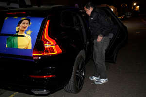 "Myanmar's Ambassador to the United Kingdom, Kyaw Zwar Minn, stands by a car with a poster of Aung San Suu Kyi, as he is locked outside the Myanmar Embassy in London on April 7, 2021. - Myanmar's ambassador in Britain on Wednesday said a Yangon miltary-linked figure had ""occupied"" the embassy in London, and that he was barred from accessing the building. ""So this is kind of a coup,"" ambassador Kyaw Zwar Minn told AFP outside the central London building, the scene of earlier protests, adding that ""defence attache, they occupy my embassy"". (Photo by Niklas HALLE'N / AFP) (Photo by NIKLAS HALLE'N/AFP via Getty Images)"