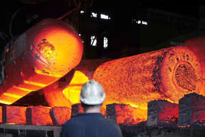a man that is on fire: Red hot metal is moved across the heavy forge at the Forgemasters Works