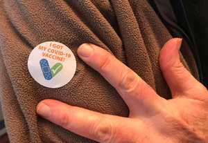 a hand holding a cell phone: A Vermonter displays his COVID-19 vaccination sticker at the DoubleTree by Hilton in South Burlington on March 4.