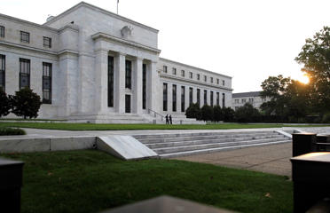 The sun rises to the east of the U.S. Federal Reserve building in Washington.