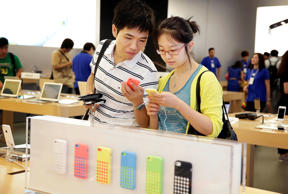 Customers look at the Apple Inc. iPhone 5c at the company's store in the Causeway Bay area of Hong Kong, China.