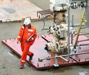 An oil worker walks at the Yastreb (Hawk) land rig at Sakhalin-1's Chaivo field, some 1,000 km (621 miles) north of Yuzhno Sakhalinsk October 10, 2006. When Exxon Mobil finishes drilling the world's longest oil well on Russia's Pacific Sakhalin island next year, it hopes to leave behind something more than just technological innovations. The world's biggest energy firm hopes that the unique technology it says it brought to Russia will help ease the Kremlin's pressure on production sharing deals with foreign majors. Picture taken October 10, 2006.