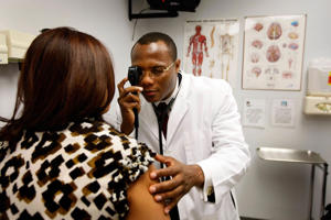A patient speaks with her doctor as he examines her at a health center in Pompano Beach, Florida.